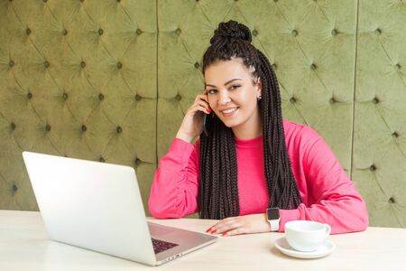 Portrait of beautiful satisfied happy young businesswoman with black dreadlock hairstyle in pink blouse sitting in cafe, talking on phone and toothy smile, looking at camera. Indoor, healthy lifestyle Banque d'images - 131854474