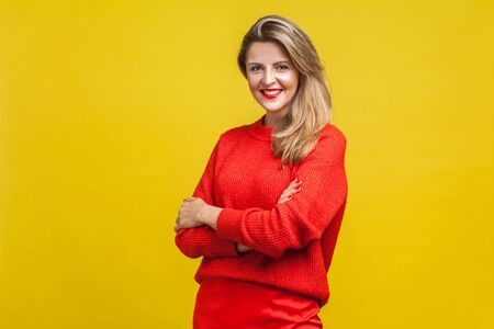 Portrait of gorgeous happy blonde woman with red lipstick in bright casual sweater standing with crossed arms and looking at camera with toothy smile. indoor studio shot isolated on yellow background