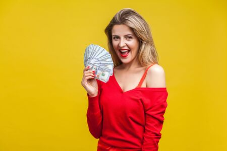 Portrait of amazed wealthy young woman in red dress standing, holding dollar bills, looking at camera with open mouth, surprised with lottery winning. indoor studio shot isolated on yellow background 스톡 콘텐츠