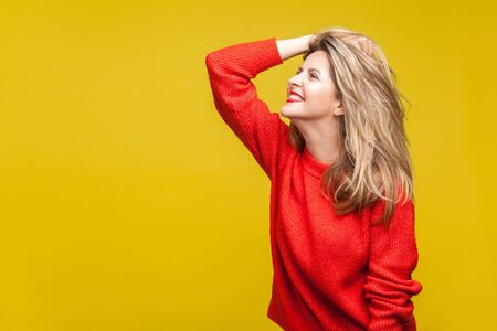 Profile side view of sensual happy blonde woman with red lipstick in casual sweater standing, touching her hair with hand and smiling, fashion model. indoor studio shot isolated on yellow background 스톡 콘텐츠