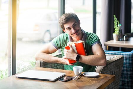 This is mine. Young happy proud businessman in green t-shirt sitting, holding and hug his favorite big red gift box, looking at camera with smile. business concept. indoor shot near window at daytime 스톡 콘텐츠
