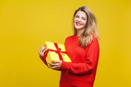 Portrait of delighted beautiful blonde woman with red lipstick in bright casual sweater, holding wrapped gift box and looking at camera, toothy smile. indoor studio shot isolated on yellow background