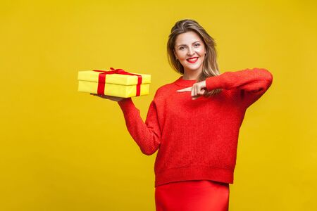 Portrait of cheerful impressive blonde woman with red lipstick in bright casual sweater, holding in hand and pointing at gift box, christmas present. indoor studio shot isolated on yellow background