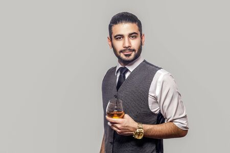 Portrait of handsome bearded brunette man in white shirt and waistcoat standing, holding glass of whiskey and looking at camera with serious face. indoor studio shot isolated on gray background.