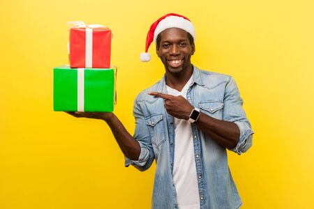Portrait of positive handsome young man in santa hat and casual denim shirt standing pointing at gift boxes and happy looking at camera, xmas shopping. indoor studio shot isolated on yellow background Stock Photo