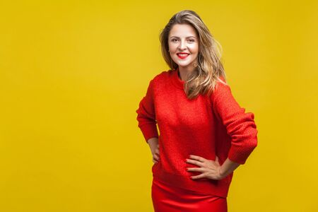 Portrait of stunning happy blonde woman with red lipstick in bright casual sweater standing with hands on hips and looking at camera with toothy smile. indoor studio shot isolated on yellow background