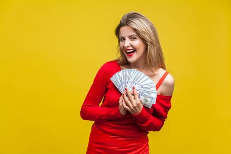 Portrait of joyous wealthy beautiful woman in red dress standing with dollar bills, looking at camera with excited toothy smile, enjoying rich life. indoor studio shot isolated on yellow background