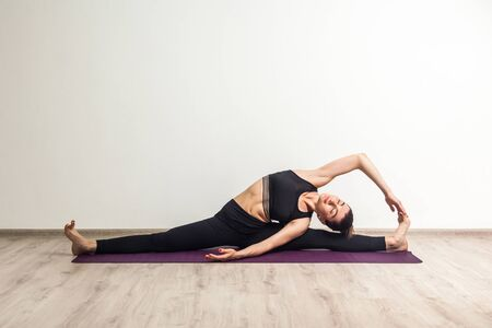 Full length portrait of young adult woman in black pants and toppracticing yoga, siting on splits and doing revolved head to knee forward exercise, parivrtta janu sirsasana pose, working out, indoor