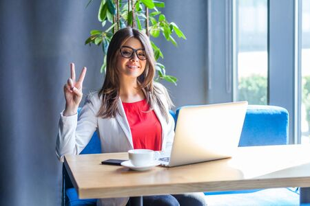 Portrait of happy beautiful stylish brunette young woman in glasses sitting and looking at camera with toothy smile, victory or peace sign. indoor studio shot, cafe, office background.