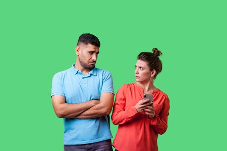 Portrait of funny resentful man in casual wear standing with crossed arms, looking disapprovingly at woman holding cellphone, addicted to internet. isolated on green background, indoor studio shot