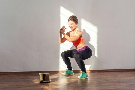 Mujer deportiva positiva con peinado de moño y en ropa deportiva ajustada haciendo ejercicio de abdominales en cuclillas mientras ve videos de entrenamiento en tableta. Foto de estudio en interiores iluminado por la luz del sol desde la ventana