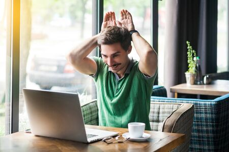 Young funny businessman in green t-shirt sitting and looking at laptop screen on video call and showing bunny ears gesture. business and freelancing concept. indoor shot near big window at daytime.