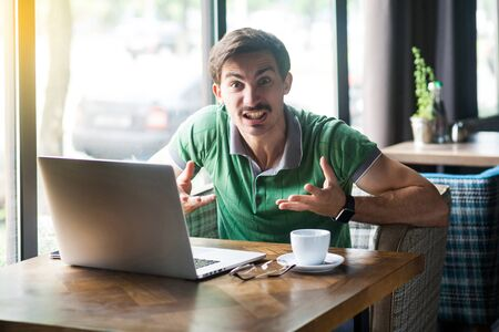 What you need? Young aggressive businessman in green t-shirt sitting and looking at camera with angry crazy face and asking. business and freelancing concept. indoor shot near big window at daytime. Stock fotó
