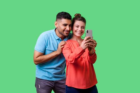 Couple in love taking picture together! Portrait of happy beautiful woman with charming toothy smile in casual clothes doing selfie with boyfriend. isolated on green background, indoor studio shot