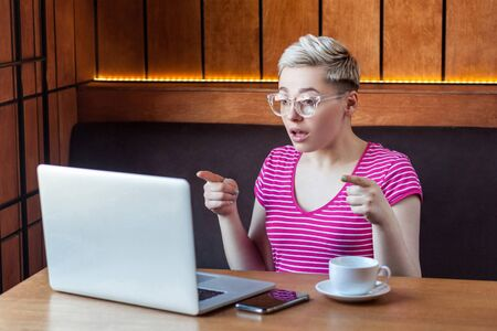 Portrait of shocked unbelievable young girl freelancer with blonde short hair, in pink t-shirt and eyeglasses is sitting in cafe, working on laptop, pointing finger to screen with shocked face