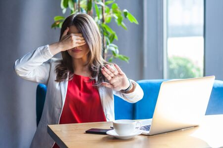 Stop, I don't want to see you. Portrait of shy or scared young woman in glasses sitting, covered her eyes with hands and don't want to look at camera. indoor studio shot, cafe, office background.