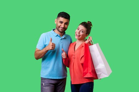 I like shopping. Portrait of satisfied young couple in casual wear showing thumbs up gesture together, cute woman holding bags and smiling widely. isolated on green background, indoor studio shot Stok Fotoğraf