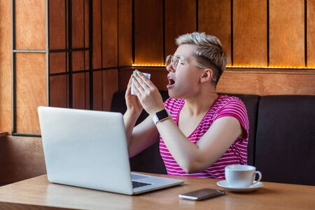 Side view portrait of illness young bussinesswoman with short blonde hair in pink t-shirt and eyeglasses sitting in cafe and holding napkin and sneeze with opened mouth, have strong flu. Indoor,health Stock Photo
