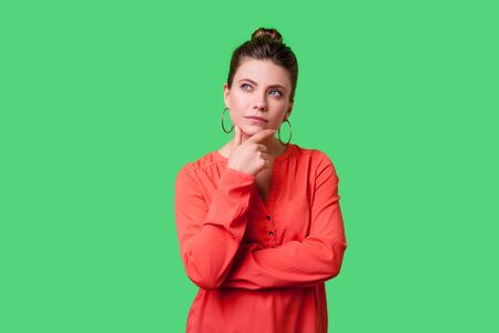 Need to think! Portrait of pensive elegant young woman with bun hairstyle, big earrings and in red blouse holding her chin and seriously thinking. indoor studio shot isolated on green background Banque d'images