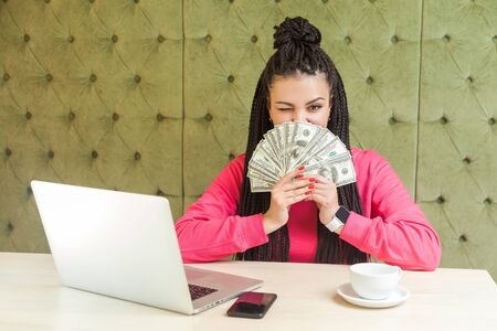 Portrait of rich attractive young adult businesswoman with black dreadlocks hairstyle in pink blouse is sitting and showing many cash dollars, covering mouth and winking. looking at camera, Indoor
