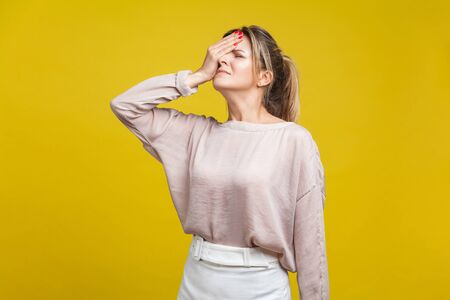 Facepalm. Portrait of regretful young woman with fair hair in casual beige blouse standing with closed eyes, covering face with hand, feeling sorrow. indoor studio shot isolated on yellow background