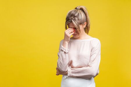 Portrait of upset young woman with fair hair in casual beige blouse standing with head down, hiding face in hand and crying, depressed and lonely. indoor studio shot isolated on yellow background