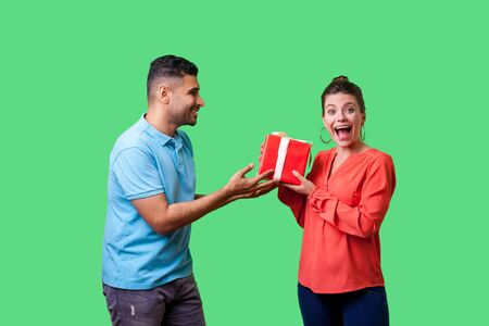 Best present for woman. Young man in casual clothes giving gift box to pleasantly surprised woman looking at camera with open mouth, unexpected bonus. isolated on green background, indoor studio shot