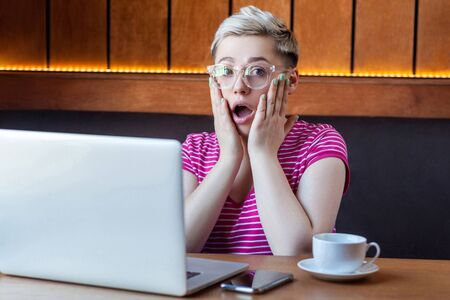 Wow! Portrait of emotional shocked young businesswoman in pink t-shirt is sitting in cafe, remotely working with suprised big eyes, open mouth and holding hands on face looking at camera.Indoor