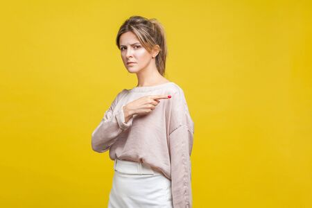 Get out! Portrait of angry young bossy woman with fair hair in casual blouse standing poiting finger out, frowning and looking at camera. you're fired. indoor studio shot isolated on yellow background