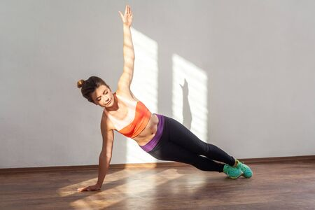 Side plank pose, yoga class. Fit woman with bun hairstyle and in tight sportswear practicing, doing handstand, concentrated with closed eyes. indoor studio shot illuminated by sunlight from window
