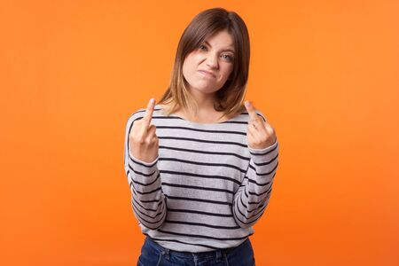 Portrait of irritated aggressive young woman with brown hair in long sleeve striped shirt standing showing middle fingers, offensive gesture at camera. indoor studio shot isolated on orange background Фото со стока - 133286568