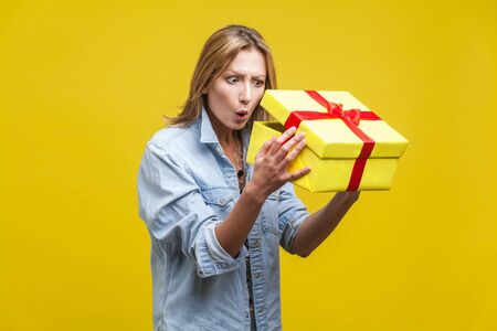 Holiday surprise. Portrait of astonished curious woman in denim shirt looking inside gift box, checking what's inside, unboxing with wow amazed expression. studio shot isolated on yellow background Фото со стока - 133286569