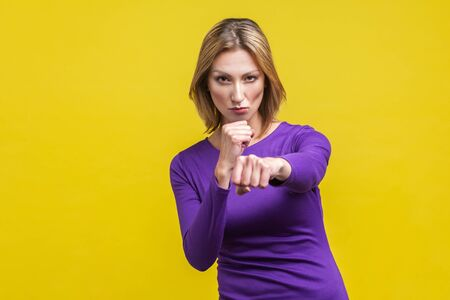 Portrait of confident purposeful businesswoman in purple dress standing holding clenched fists ready to boxing, strong spirit to fight for the goal. indoor studio shot isolated on yellow background Фото со стока - 133286571
