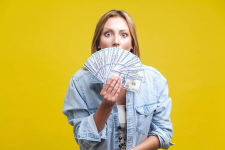 Portrait of surprised young woman in denim shirt peeking out of dollars fan, hiding her half face and looking at camera with big amazed eyes. indoor studio shot isolated on yellow background Фото со стока - 133286575