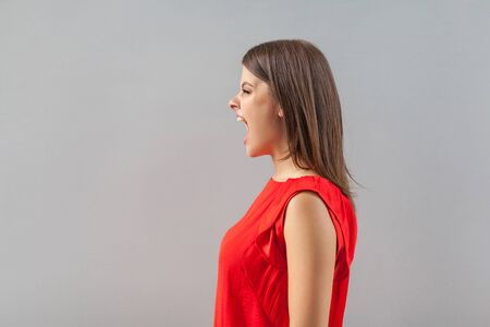 Profile side view portrait of crazy wild aggressive brunette young woman in red shirt standing, looking forward and screaming or yelling. indoor, studio shot, isolated on gray background. Фото со стока - 133286584
