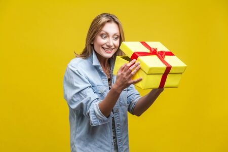 Long awaited present. Portrait of curious woman in denim shirt looking inside gift box, checking what's inside, unboxing with satisfied happy expression. studio shot isolated on yellow background Фото со стока - 133286586