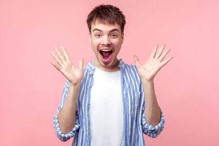 Unbelievable news! Portrait of shocked brown-haired man with big eyes and open mouth raising hand, looking at camera with stunned astonished face. indoor studio shot isolated on pink background Фото со стока - 133286528