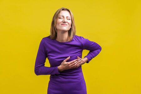 Portrait of sick woman in elegant tight purple dress suffering from pain in chest, grimacing with closed eyes, risk of heart attack or breast cancer. indoor studio shot isolated on yellow background
