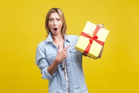Wow, what a surprise! Portrait of amazed woman with fair hair in denim casual shirt pointing at wrapped gift box and looking with amazement, shocked by holiday present. studio shot isolated on yellow Фото со стока - 133286532