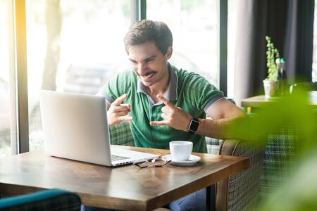Yes. Young happy excited businessman in green t-shirt sitting, working and looking at laptop screen with rock sign and cheering. business and freelancing concept. indoor shot near window at daytime.