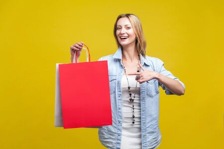 Join shopping! Portrait of cheerful shop customer, happy woman pointing at bags and looking at camera with toothy smile, satisfied with discounts. indoor studio shot isolated on yellow background Фото со стока - 133286529