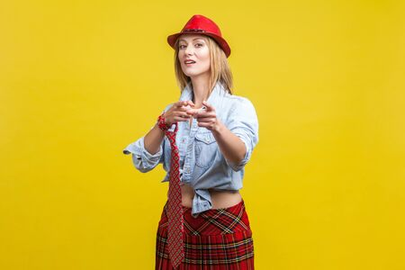 Portrait of beautiful glamorous woman wearing stylish red hat, school skirt and tie knotted on hand, pointing fingers at camera. showing hey you gesture. studio shot isolated on yellow background