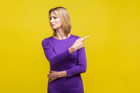 Get out! Portrait of angry bossy woman in elegant tight purple dress looking aside and pointing finger another way, asking to leave, dissatisfied expression. indoor studio shot isolated on yellow Фото со стока - 133286534