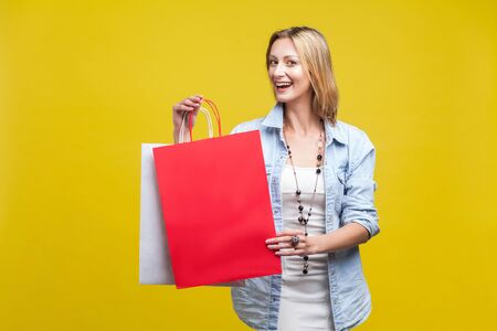 Shopping time! Portrait of satisfied shop customer, happy woman holding bags and looking at camera with charming toothy smile, rejoicing discount. indoor studio shot isolated on yellow background Фото со стока - 133286548