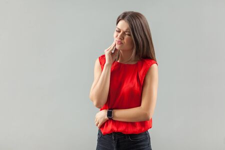 toothy ache. Portrait of upset brunette young woman in red shirt standing, touching her cheek because feeling pain on her teeth . indoor, studio shot, isolated on gray background.