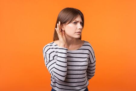Portrait of attentive nosy young woman with brown hair in long sleeve striped shirt standing, keeping hand near ear and listening secret information. indoor studio shot isolated on orange background 스톡 콘텐츠