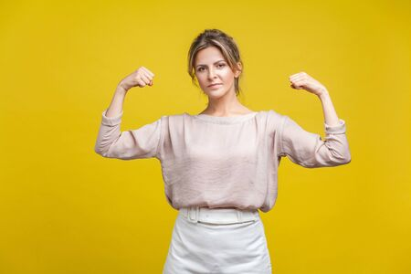 I am strong and independent. Portrait of confident woman with fair hair in casual blouse standing, showing biceps as demonstrating female power. indoor studio shot isolated on yellow background Фото со стока - 133286542