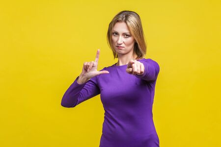You are loser! Portrait of bossy serious businesswoman in elegant purple dress showing loser gesture and pointing at camera, accusing for failure. indoor studio shot isolated on yellow background Reklamní fotografie