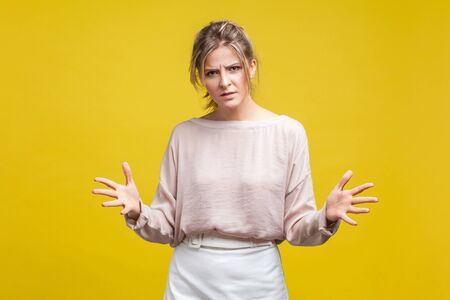 How could you? Portrait of annoyed disappointed woman with fair hair in casual blouse standing with raised arms, frustrated and angry while arguing. indoor studio shot isolated on yellow background