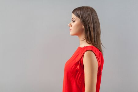 Profile side view portrait of serious calm beautiful brunette young woman in red shirt standing and looking forward with serious face. indoor, studio shot, isolated on gray background. Фото со стока - 133286553